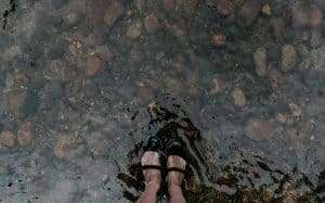 sandaled feet in water
